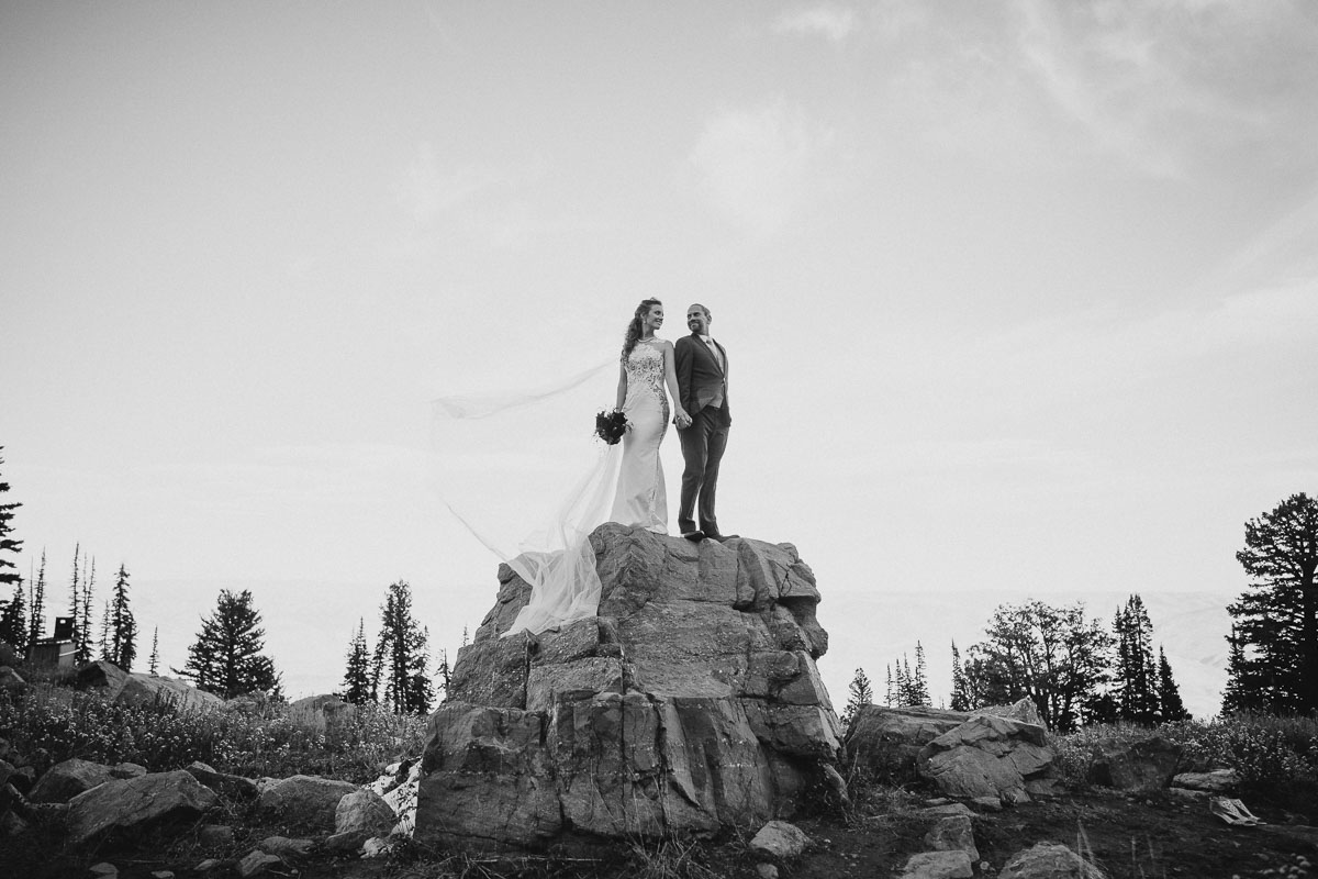 Snowbasin wedding black and white bride and groom on rock perch photo