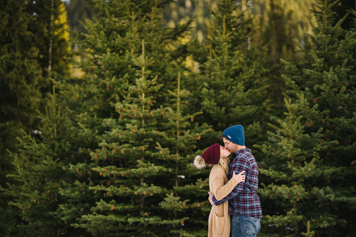 Donut Falls engagement couple in beanie hats kissing photo