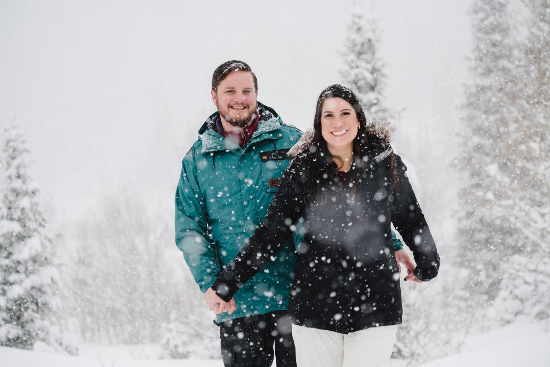 Big Cottonwood Canyon engagement couple walking through snow Donut Falls photo