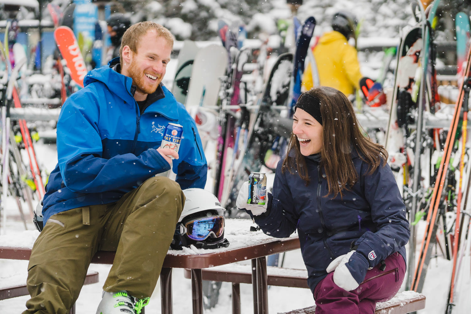 ski engagement session couple laughing at snowy picnic table photo