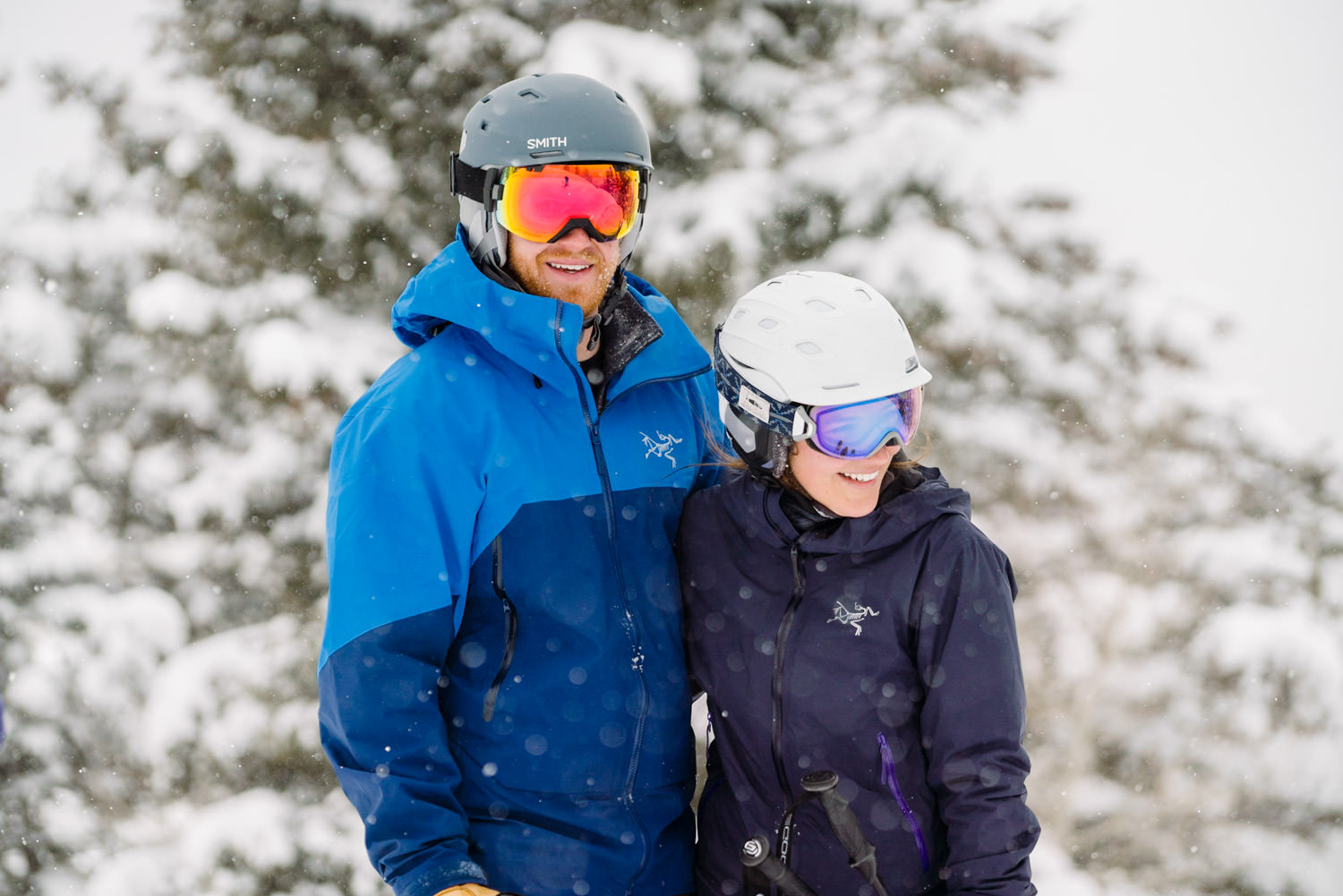 ski engagement session couple laughing in helmets and goggles photo