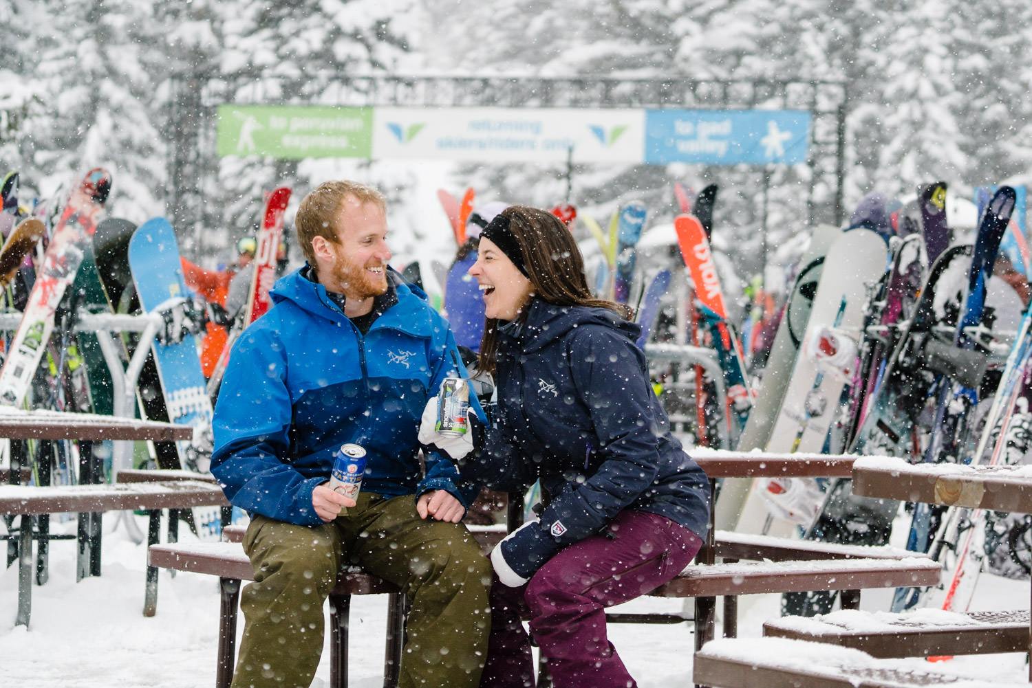 ski engagement session couple laughing in snowflakes photo