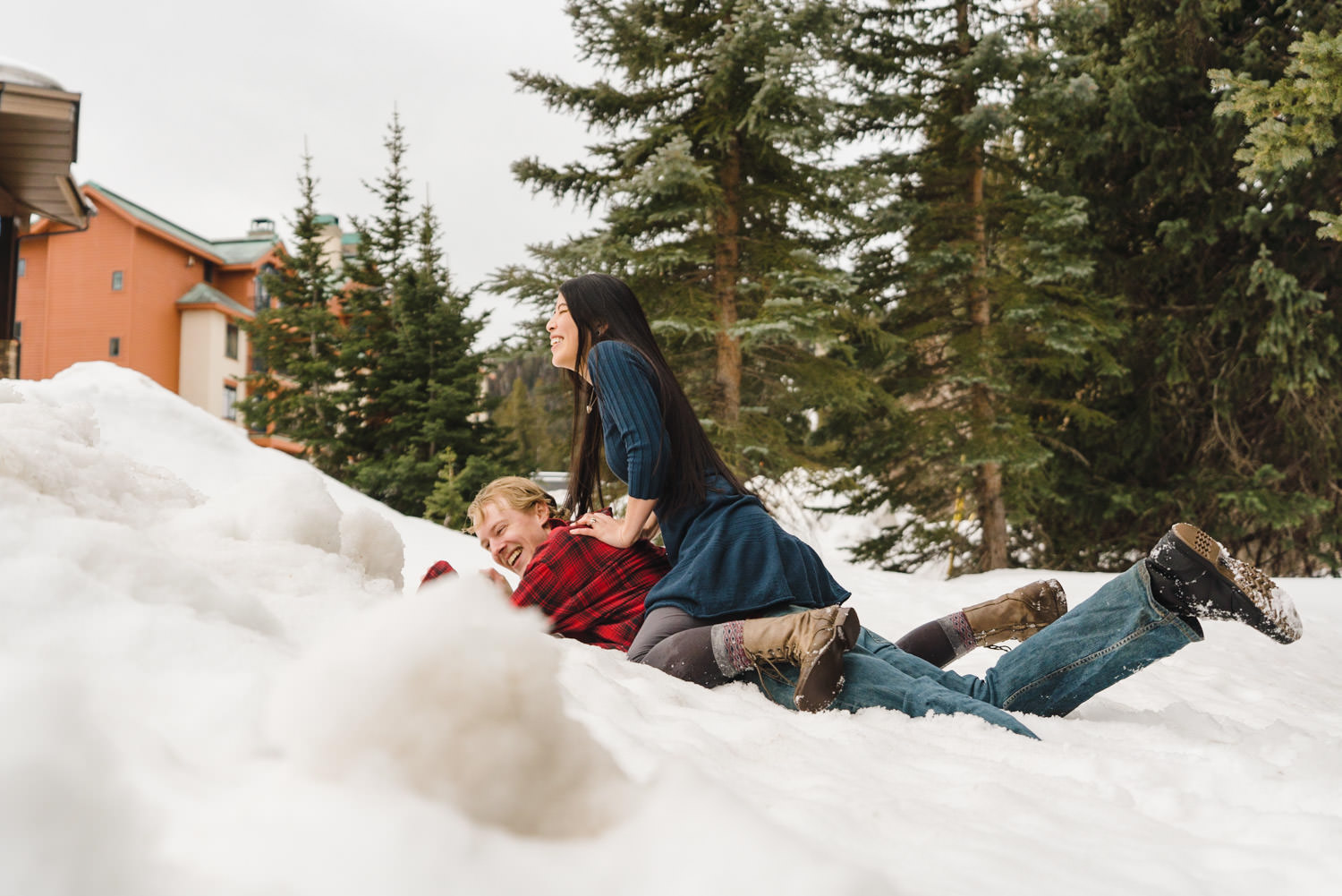 Engagement session at Solitude laughing laying down in snow photo
