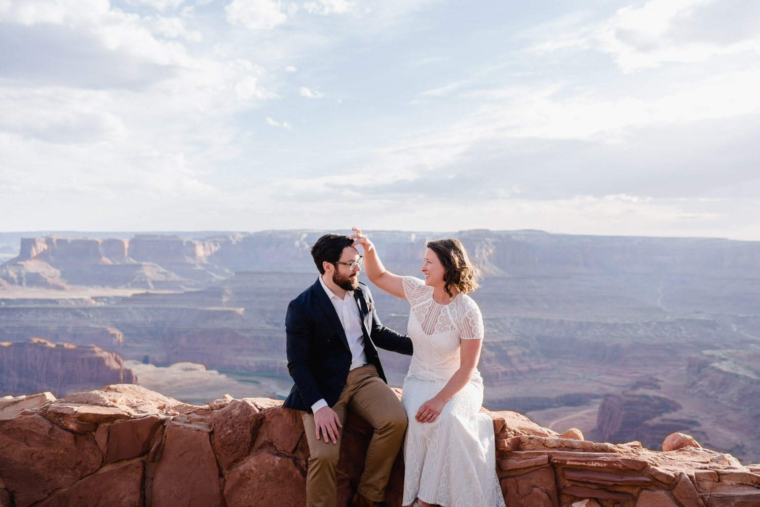 Dead Horse Point elopement bride fixing groom's hair photo