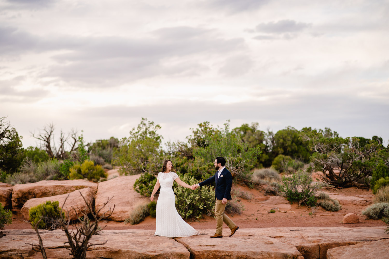 Dead Horse Point elopement bride and groom holding hands photo