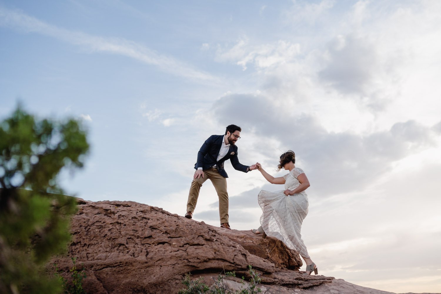 Dead Horse Point elopement groom helping bride up rocks photo