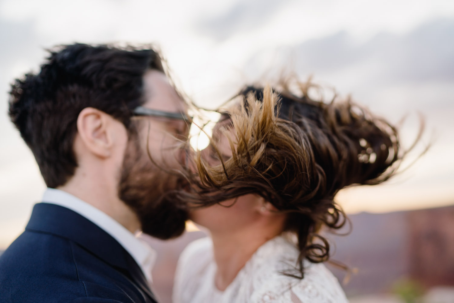 Dead Horse Point elopement kiss with wind in the hair photo