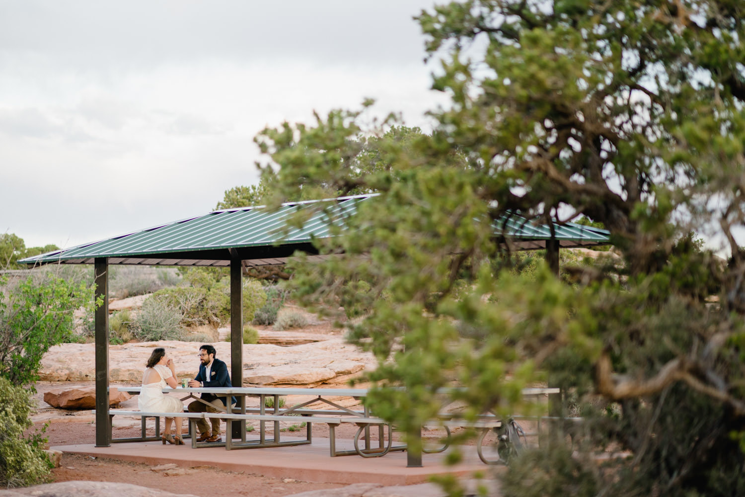 Dead Horse Point elopement bride and groom talking under shelter photo