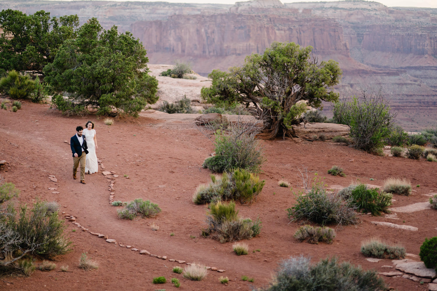 Dead Horse Point elopement couple walking rock lined path photo
