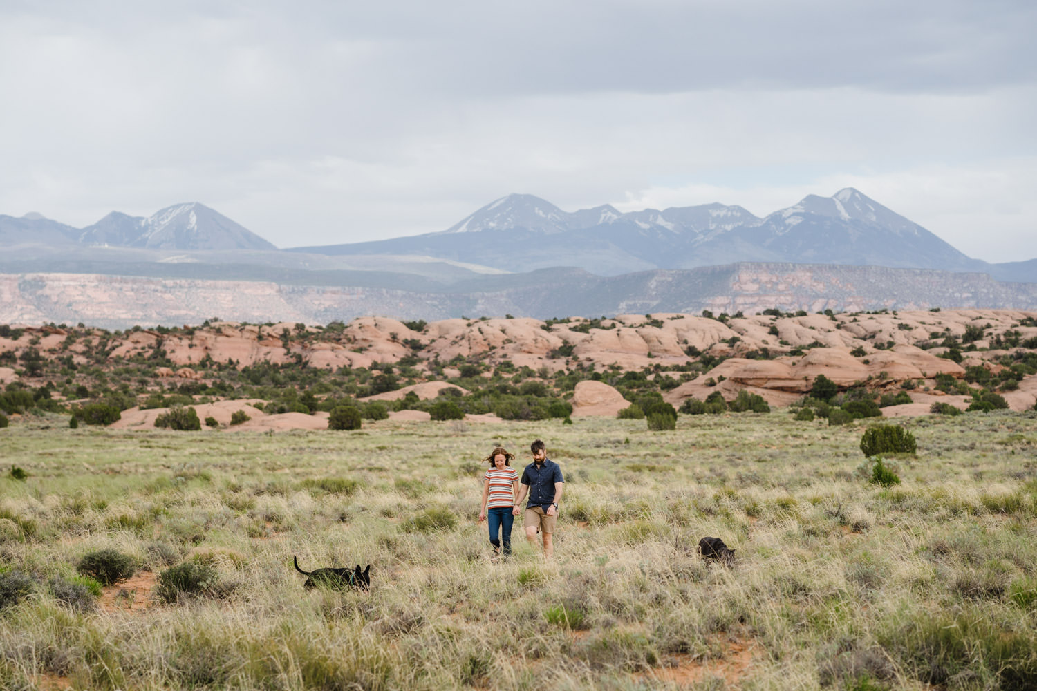engagement session in Moab couple walking with dogs photo