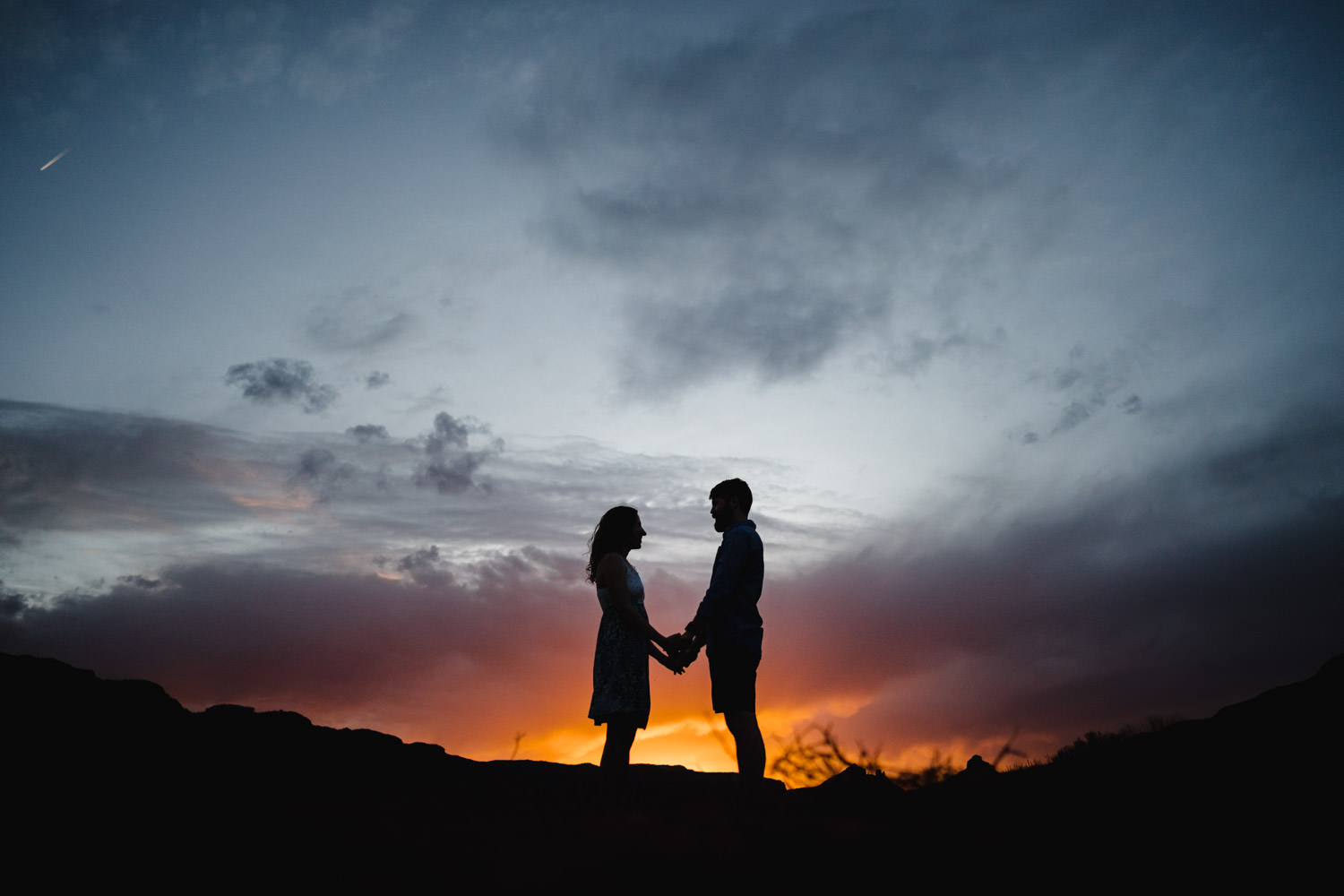 engagement session in Moab holding hands with sunset photo