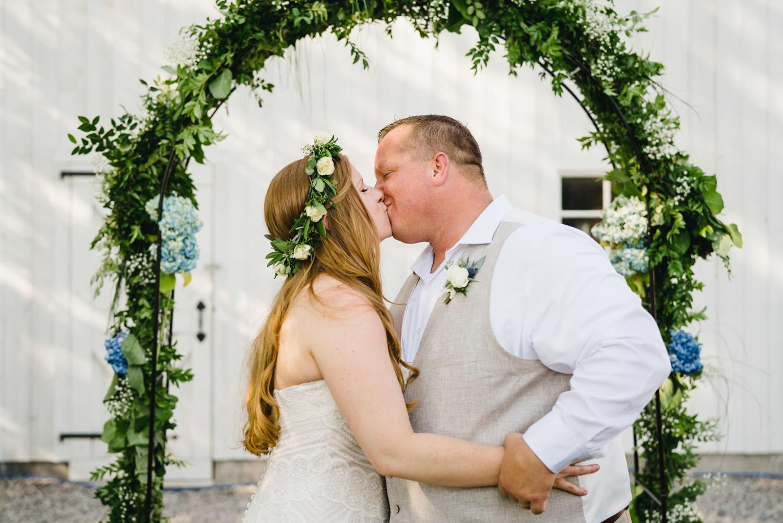 Spring Farm wedding couple kisses under the arch photo