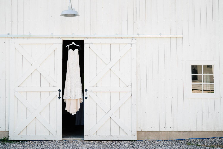Spring Farm wedding dress hanging between barn doors photo
