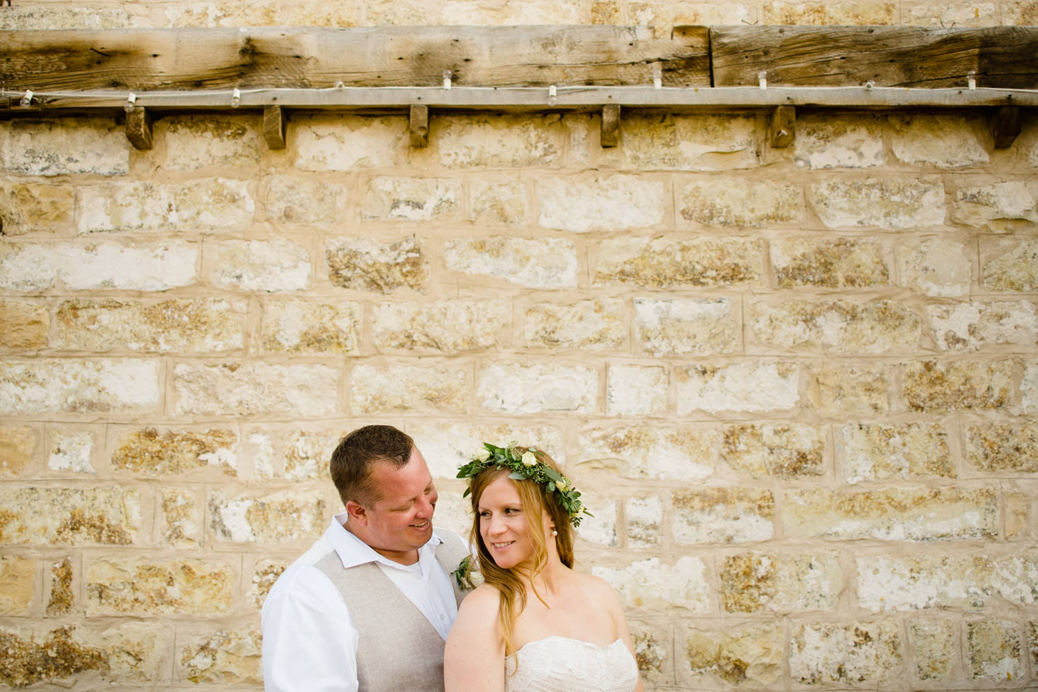 Spring Farm wedding couple smiling against historical building wall photo