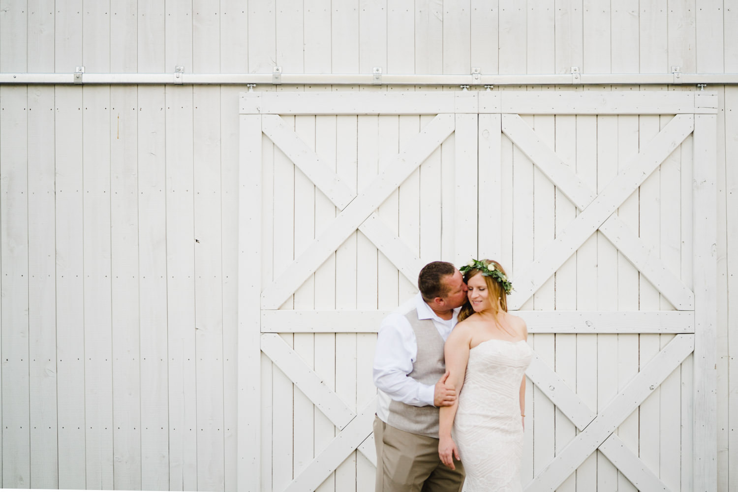 Spring Farm wedding kissing in front of white barn photo