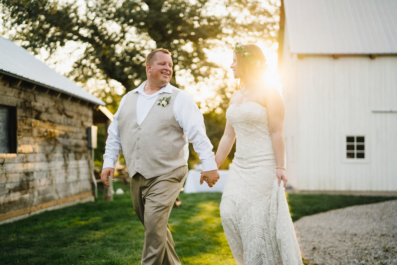 Spring Farm wedding holding hands with sunbeam photo