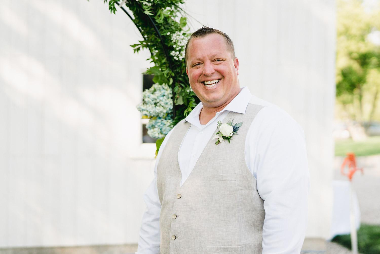 Spring Farm wedding groom smiling as bride arrives photo