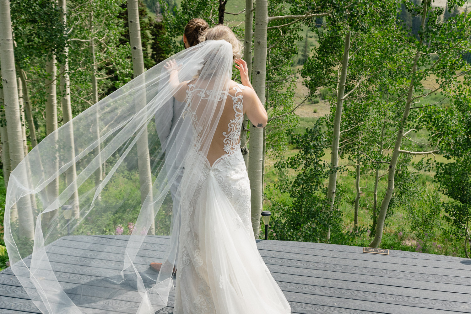 brides train blowing in wind and groom standing out by trees