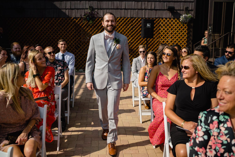 groom walking down aisle smiling alta lodge wedding