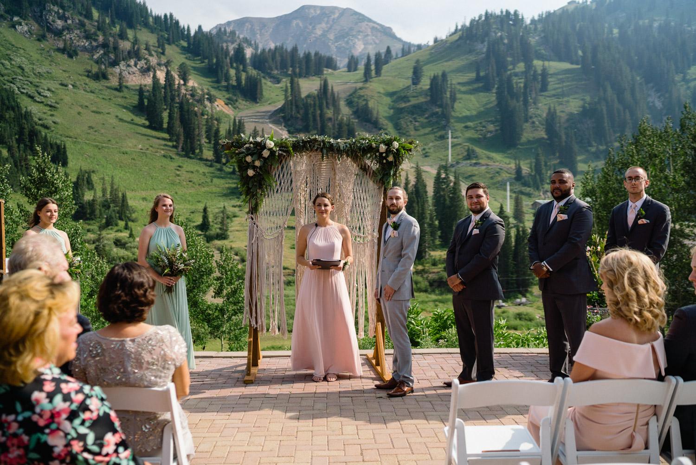 wedding party watching bride walk down aisle mountain resort view alta