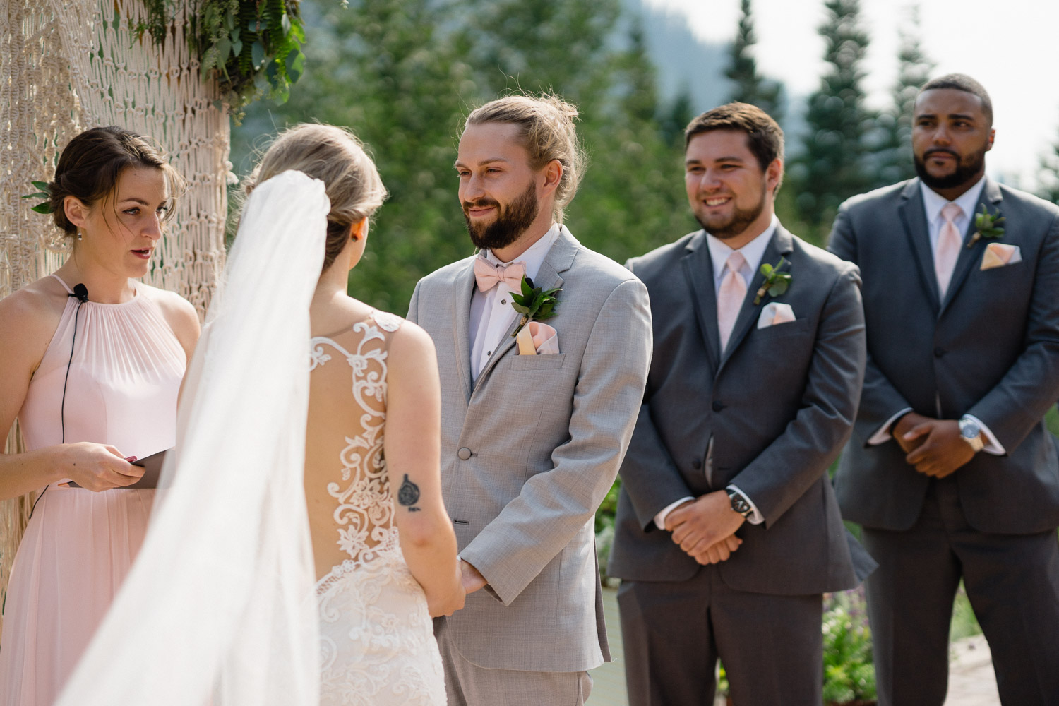 groom smiling at bride with officiant and grooms men alta resort