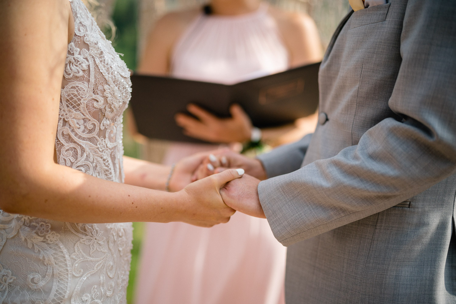 bride and groom ceremony close up holding hands