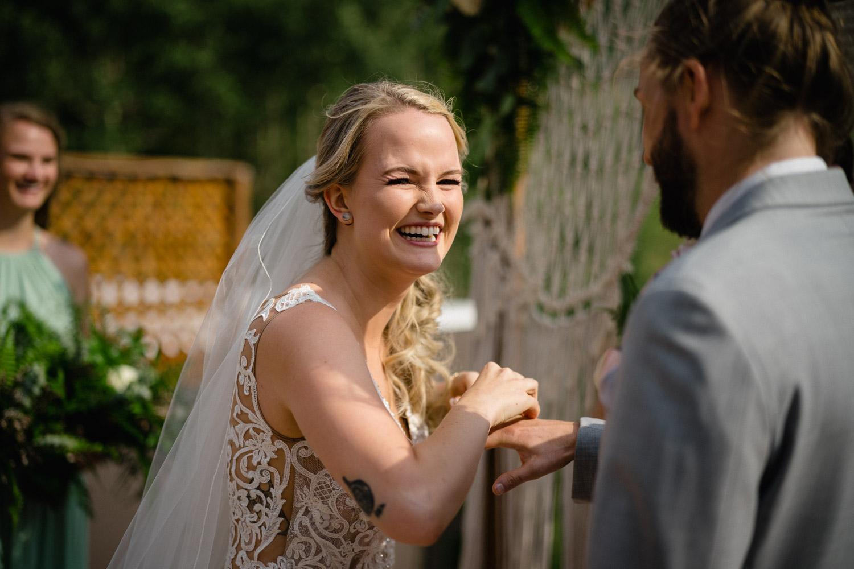 joyful bride laughing putting ring on groom alta resort