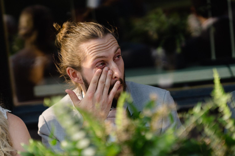 groom wiping tears outdoor wedding alta
