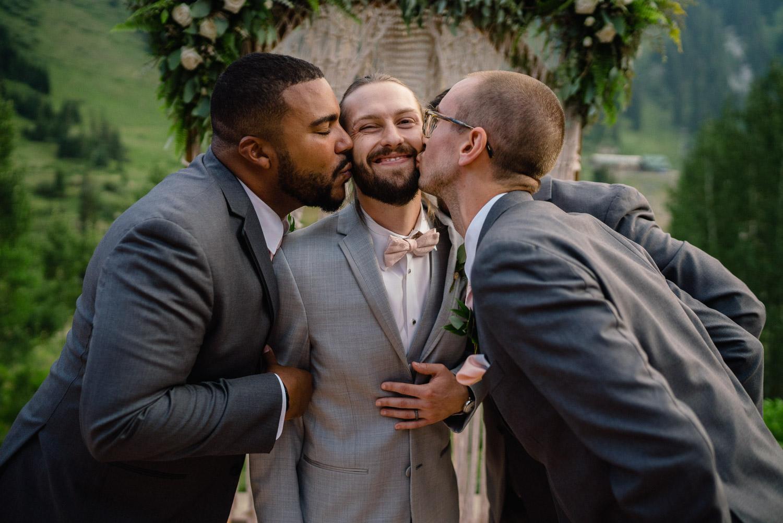 groomsmen kissing groom on cheek alta lodge wedding