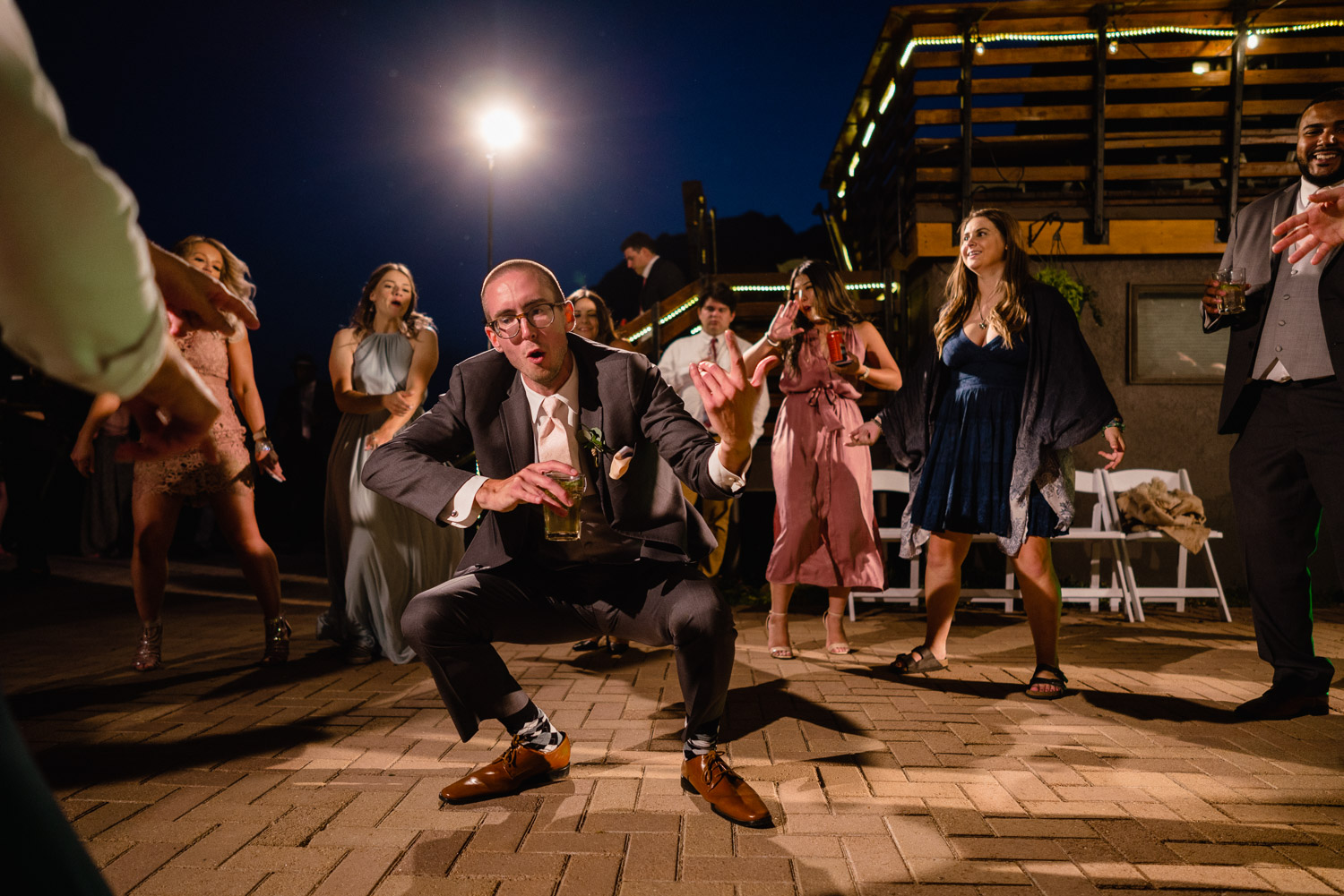 guests dancing on deck outside at night wedding