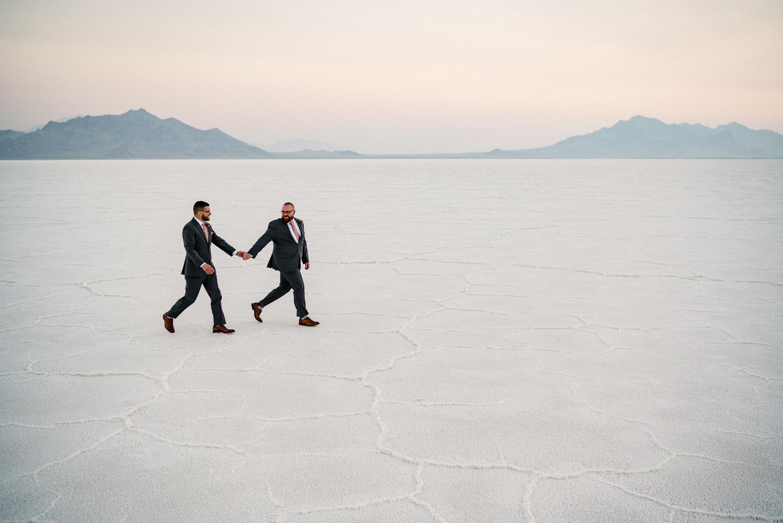 grooms walking holding hands salt flats
