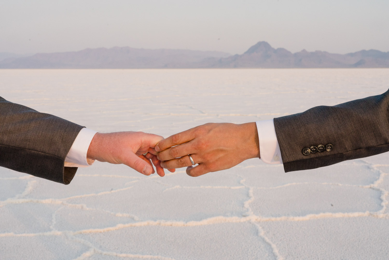 grooms hand in hand wedding ring salt flats