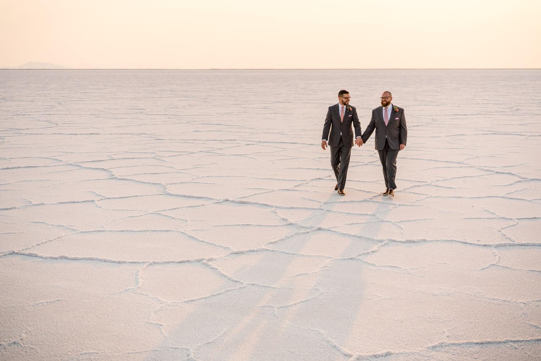 grooms holding hands walking on salt flats