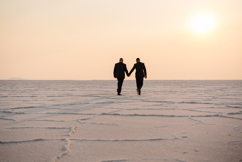 grooms walking toward sun salt flats