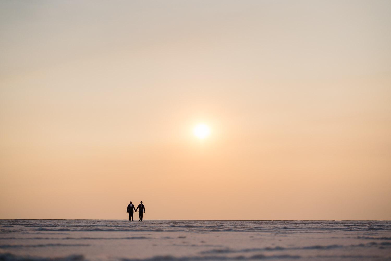 grooms walking toward the horizon salt flats