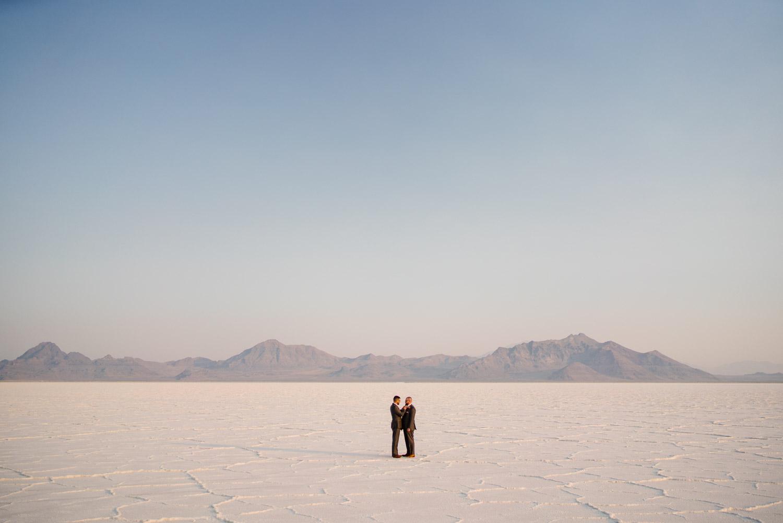 grooms embracing in distance salt flats