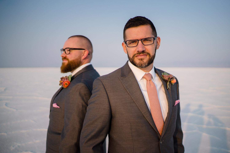 grooms standing back to back salt flats wedding