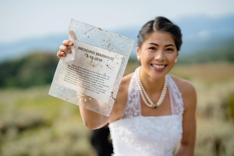 bride holding wedding warning notice outside dirt wedding