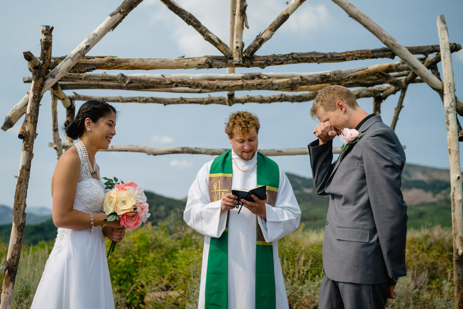 bride groom and officiant at outdoor altar groom wiping eyes