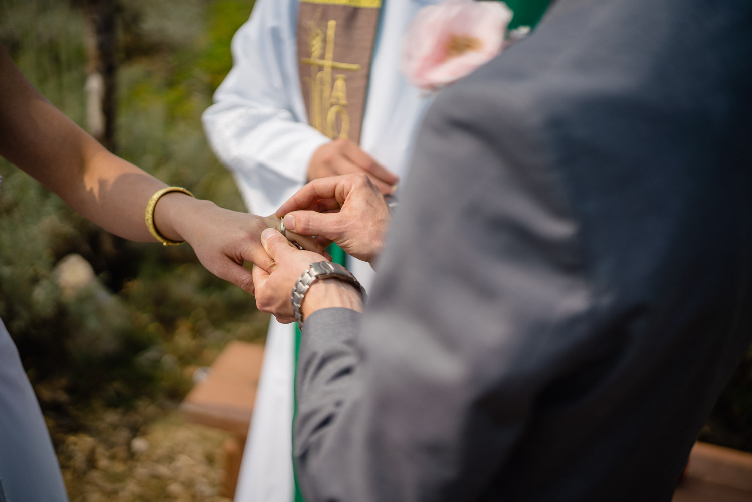 groom putting ring on bride at outdoor altar