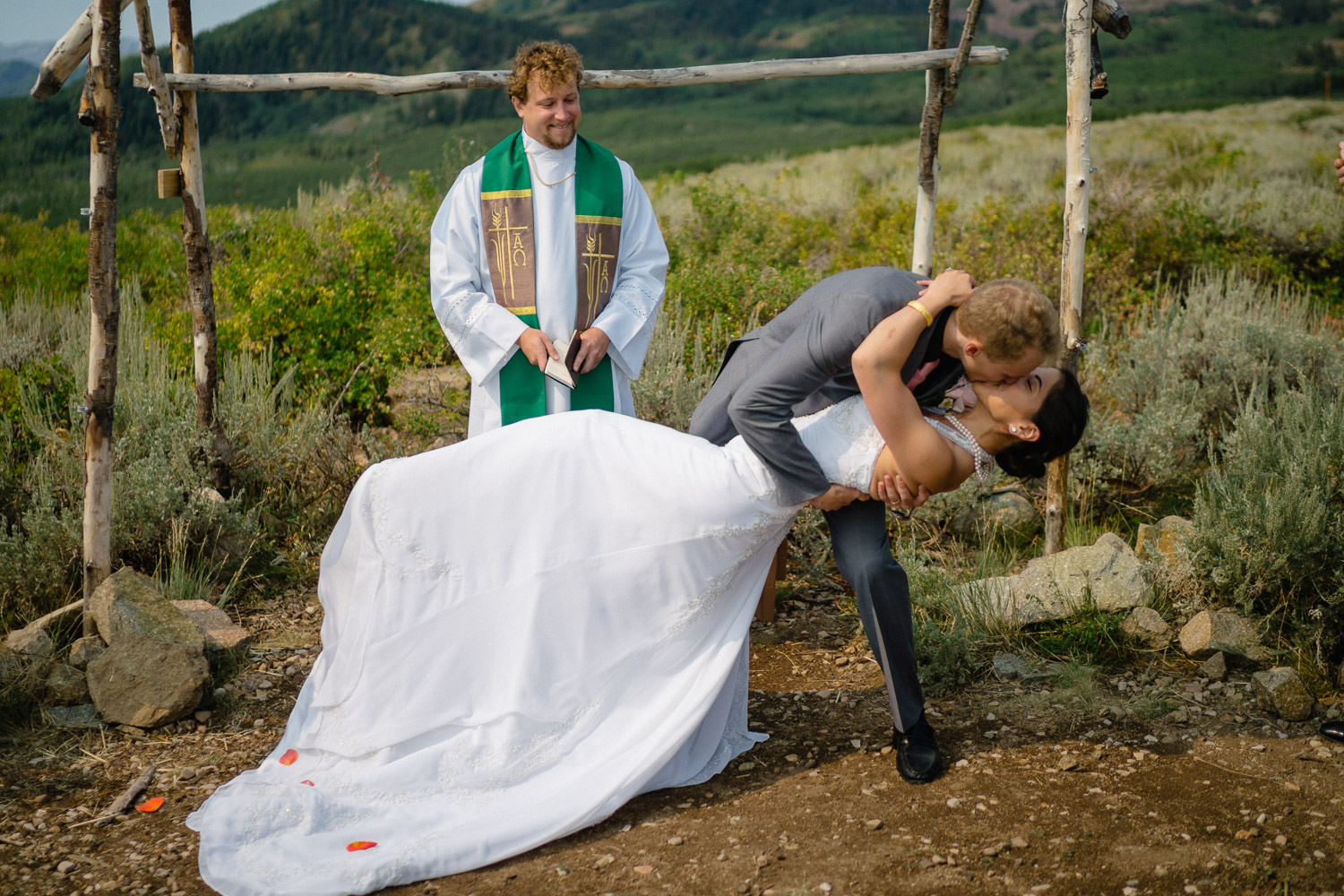 groom dipping and kissing bride outside wedding ceremony