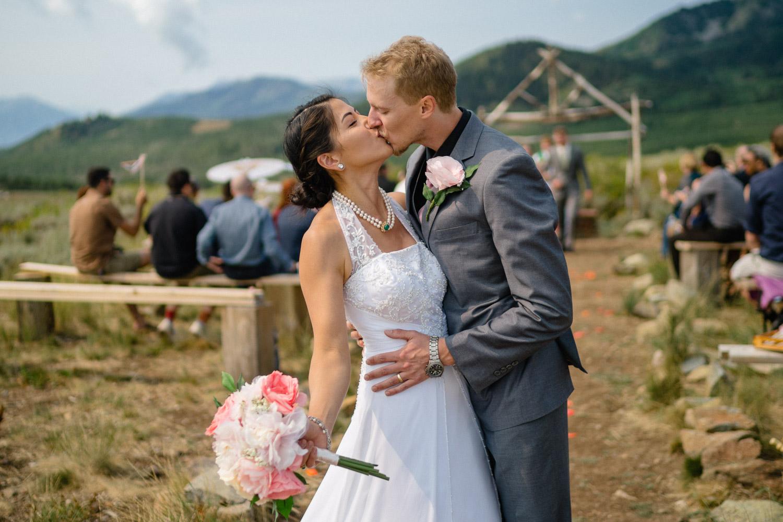 groom kissing bride after outdoor wedding