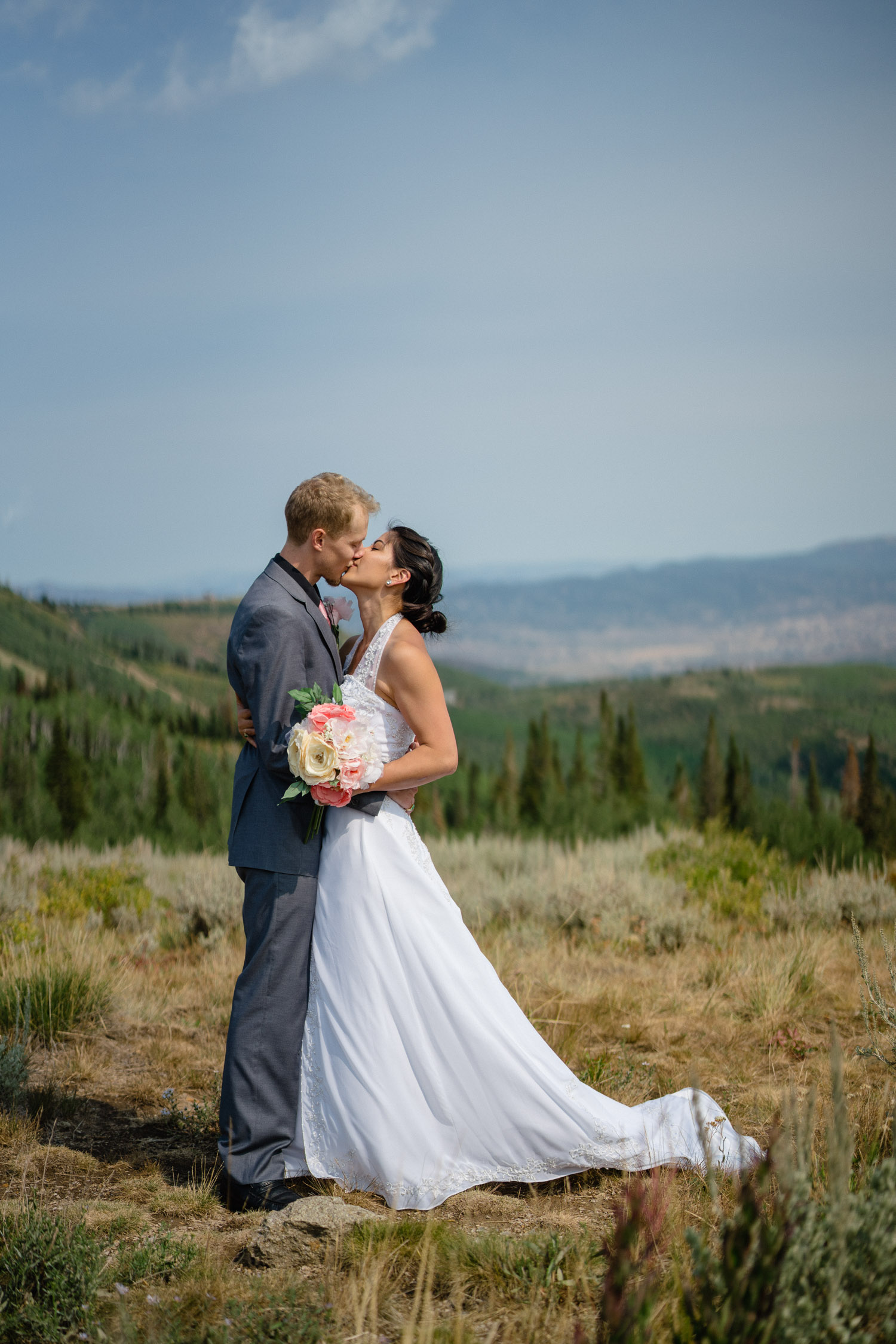 bride and groom kissing outside under blue sky