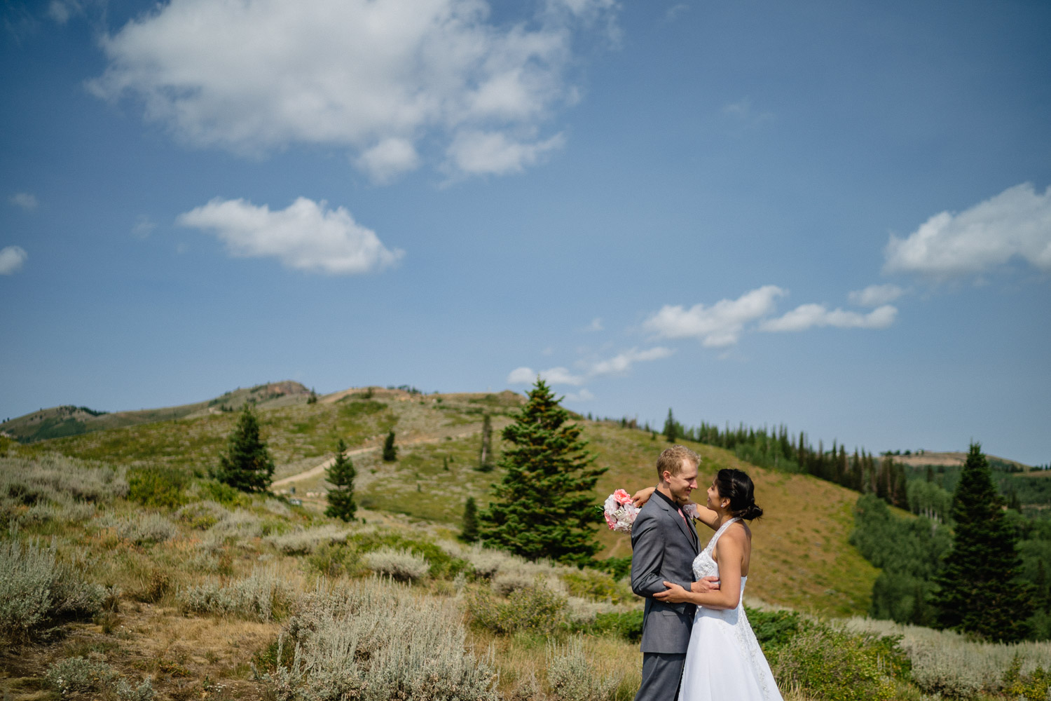 bride and groom hugging on mountain under blue sky