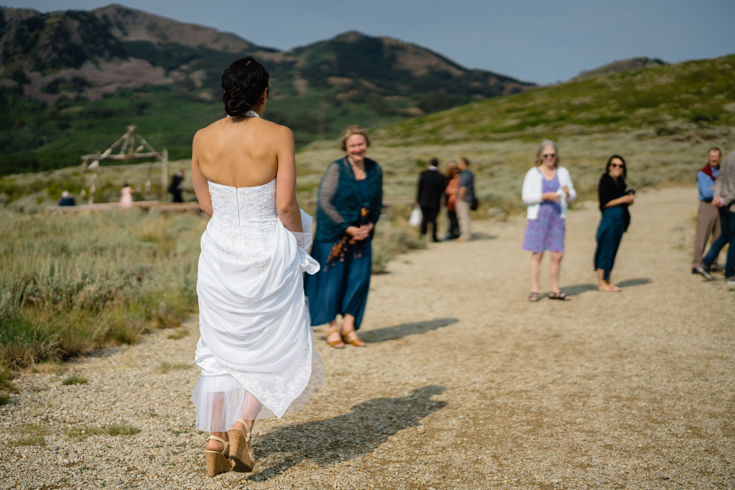 bride walking down dirt path to wedding guests