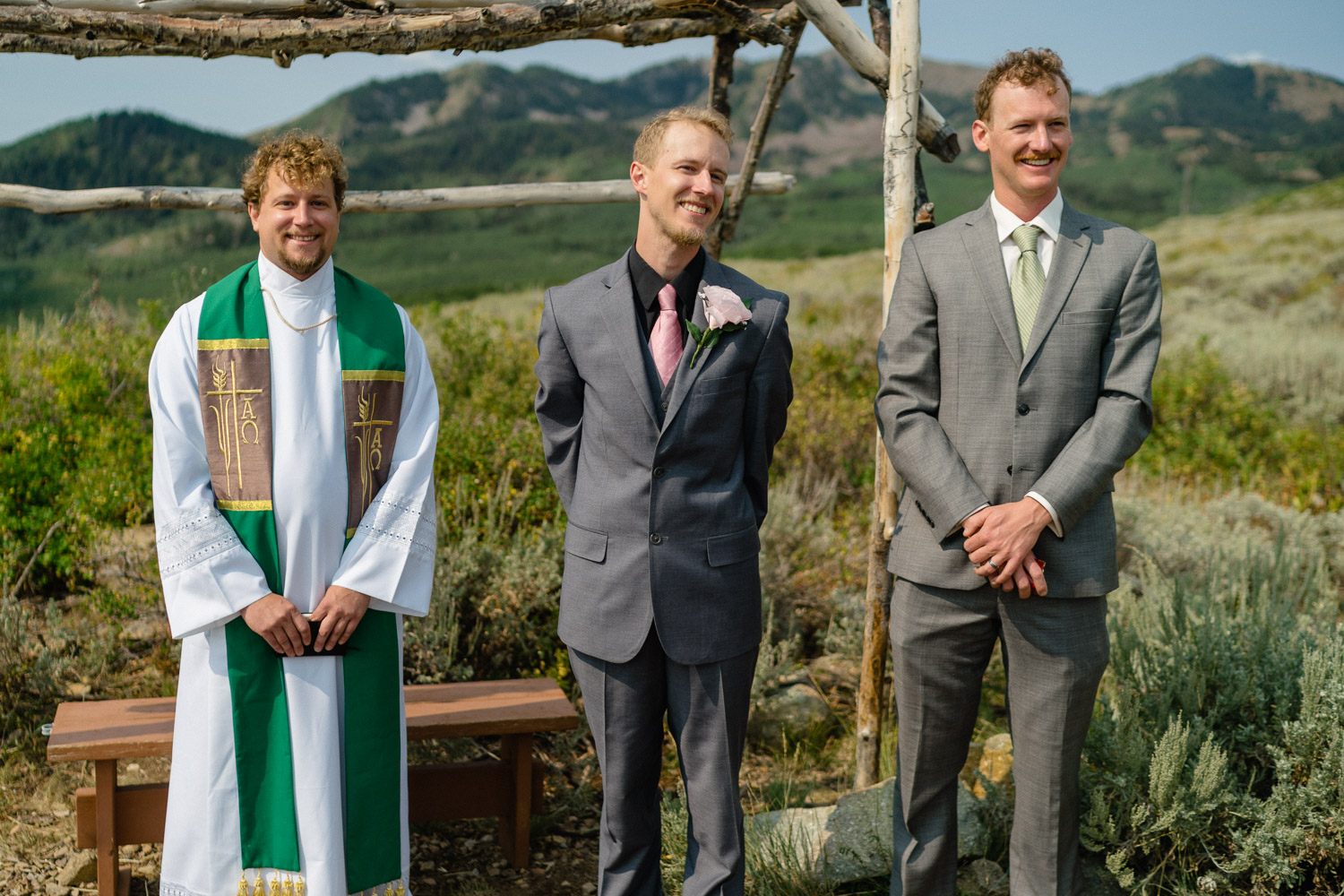 groom officiant and grooms men smiling at bride walking down aisle outside