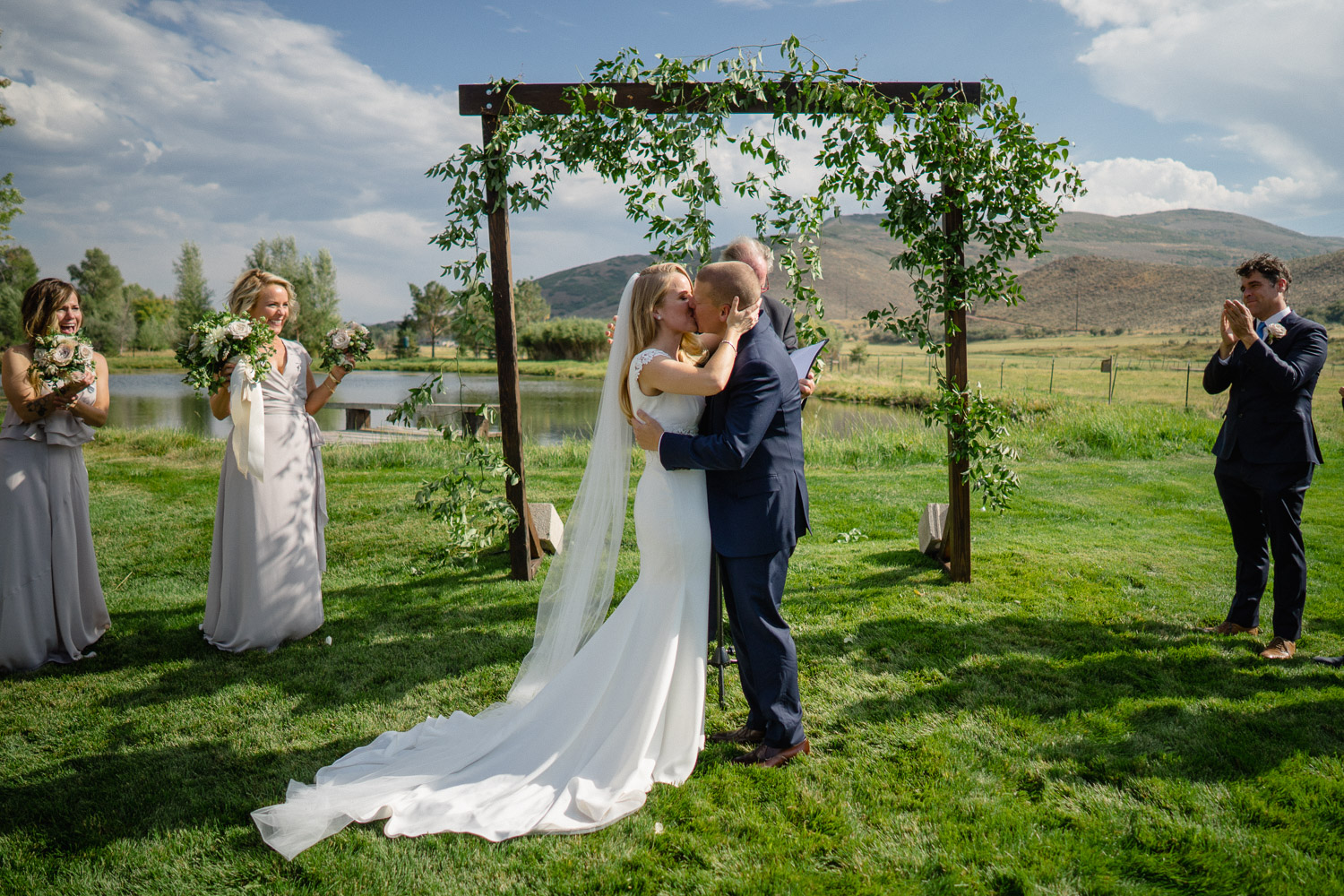 bride and groom first kiss outdoor altar park city wedding