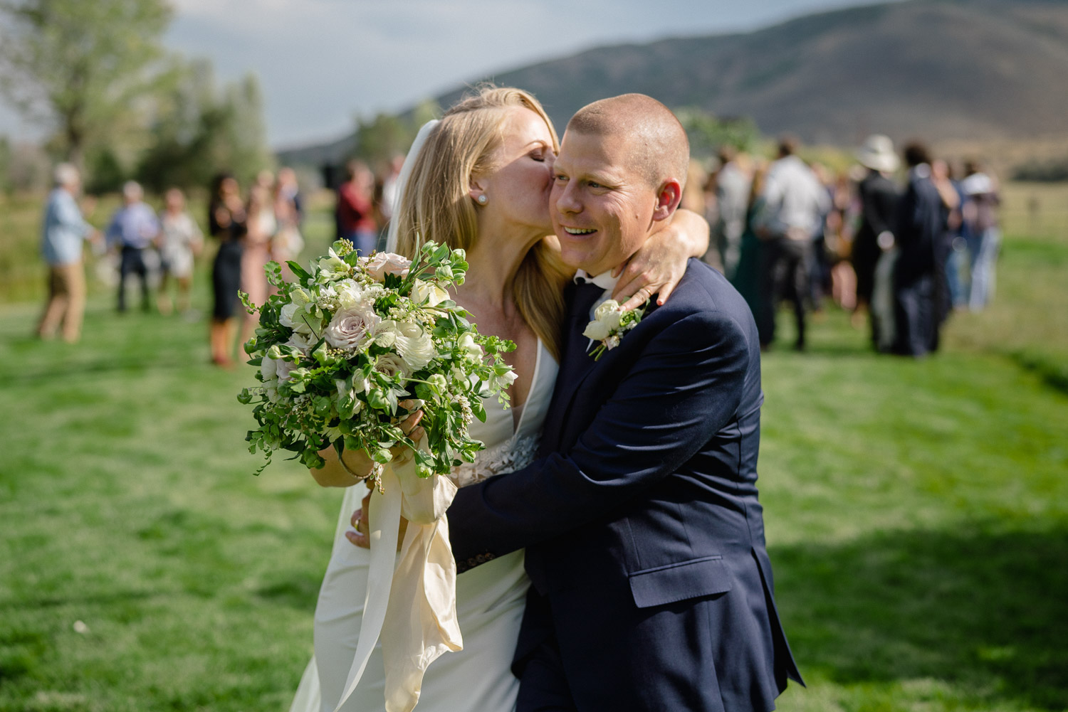 bride kissing groom on cheek guests in background park city wedding