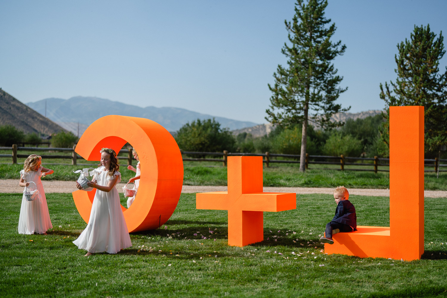kids sitting on bride and groom's initials in yard park city wedding
