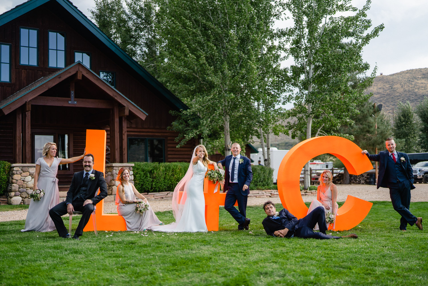 wedding party posing on outdoor lettering decoration in yard park city wedding